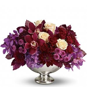 Spectacular red cymbidium orchids, purple mokara orchids, lavender hydrangea, crème roses, dark red spray roses, burgundy dahlias, purple and lavender chrysanthemums and burgundy copper beech arrive in an exclusive Mercury Glass Bowl.