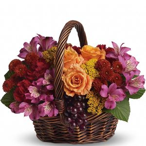 The basket overflows with orange roses and spray roses, maroon carnations, purple alstroemeria, burgundy button spray chrysanthemums, yarrow and even a bunch of grapes (not real, of course)!