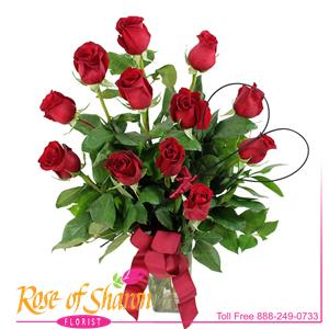 Beautiful Red Velvet Roses arranged with salal in a classic, tapered glass vase.