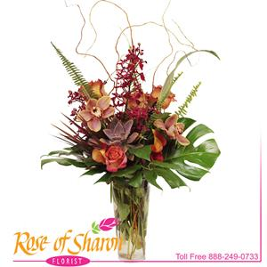 Mason, a statuesque vase design of succulents, fiery roses, cymbidium and James Story orchid arranged with flax and monstera in our French flute vase. Originally designed for Marian Regional Medical Center's 5-year anniversary and now a popular gift in our catalog.