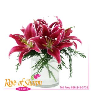A heavy, glass cylinder, frosted to evoke moments of winter, filled with stunning Oriental lilies and fragrant juniper.
