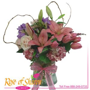 A lush and low vase of tulips, roses, fragrant freesia, hydrangea and heather in a gathering vase.