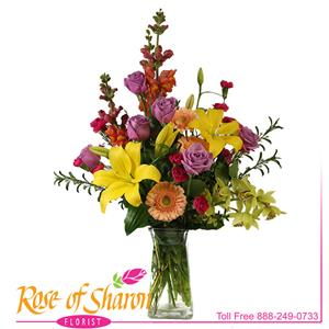 Mae Vase arrangement is a sparkling bouquet of bright, fresh botanicals such as yellow Asiatic lily, peach Gerbera, fragrant lilac roses, lime green Cymbidium, snapdragons and mini-dianthus in a tall, forward focused arrangement.