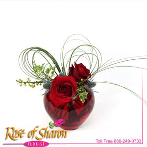 Two Red Velvet Roses arranged in a distintive red glass heart and finished with a heart fashioned of bear grass. An affordable expression of young love in a keepsake quality glass vase.