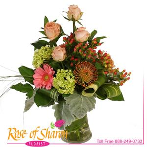 Peach Roses, orange Hypericum and Apricot Gerbera along with miniature green Hydrangea and spider Protea are gathered in a sculpted vase to create Brooke.