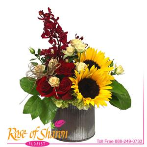 Natsumi speaks of Summer's Beauty. This rustic bouquet of vibrant, deep hues in Sunflower, Hydrangea, Roses and blushing bride Protea arranged in our Nora corrugated tin container.
