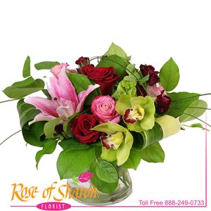 Delaney Bouquet is a collection of ruby and deep pink roses, garnet spray roses and soft pink, frangrant Oriental Lilies arranged in a short cylinder vase and finished with two striking Cymbidium Orchid blooms.