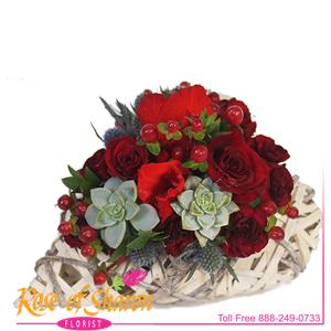 Elizabeth is a delicate collection of romantic red roses, sweet wine-colored hypericum berries and miniature succulent arranged in a heart-shaped garden basket. Highly detailed and preciously romantic.