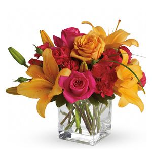 Orange roses, hot pink roses, spray roses and carnations are joined by glowing orange asiatic lilies and bear grass in a delightful vase. This unique arrangement is delivered in a cube but it's definitely not for squares.