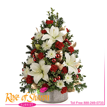 "Jordan Christmas Tree is a classic table-top boxwood and evergreen ""tree"" created of fresh-cut evergreens, lily, minature dianthus and finished with seasonal holiday decorations. Shown arranged in Norah Bowl."