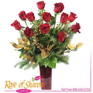 Yule Rose Bouquet combines twelve premium roses with gilded salal, eucalyptus and golden fir branches in a red glass vase.