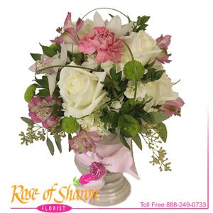Mackenzie is a soft bouquet of pastel and cré blooms such as dianthus, alstromeria, orchid, hydrangea and roses designed in a ceramic pedestal vase. Finished with double-faced satin ribbon and a small metal pillow heart.