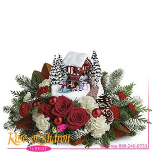 Set atop a magnificent bouquet of festive flowers and fresh Christmas greens, this light-up, hand-painted Thomas Kinkade collectible will brighten your holidays for years to come! This lush bouquet includes red roses, white carnations, red miniature carnations, and white miniature carnations, accented with flat cedar, magnolia leaves, and noble fir.